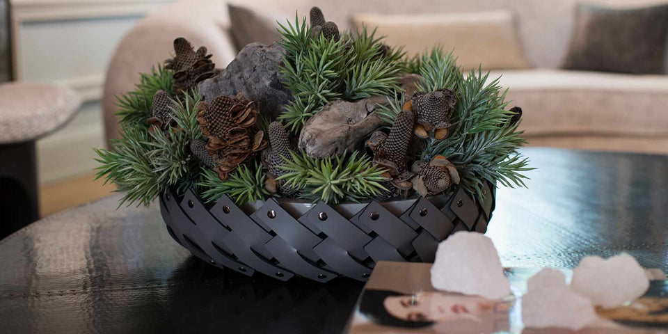 Arrangement of succulents, driftwood pieces and dried banksia in hand-woven Italian shallow basket
