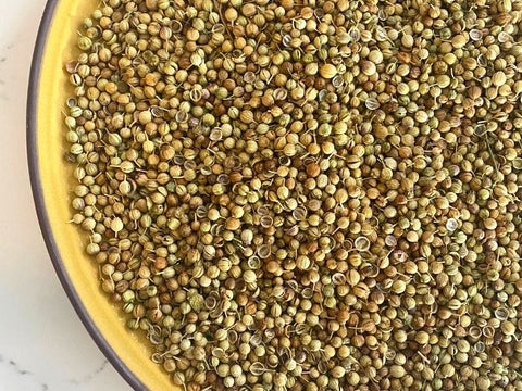 whole coriander seeds in yellow plate on marble counter