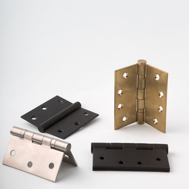 Group of 4 door hinges together in brass, steel, and black finishes. In different positions.