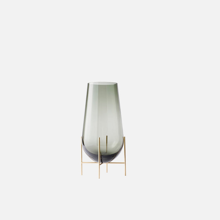 Small clear glass vase sitting on beautiful bronze legs.