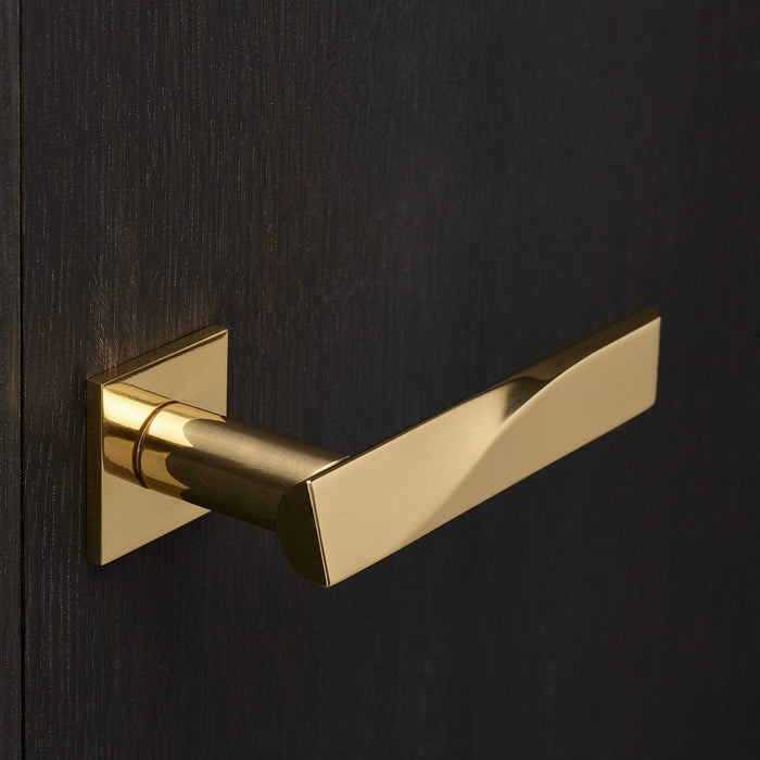 Elegant brass lever handle with square rose on dark wood door. Beautifully and functionally designed.