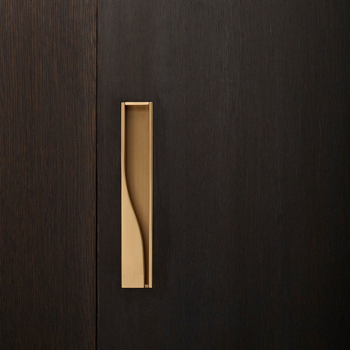 Elegant brass sliding door handle on dark wood from the front. Beautifully and functionally designed.