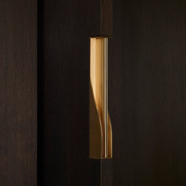 Elegant brass dressing handle on a dark wood door from an angle. Beautifully and functionally designed.