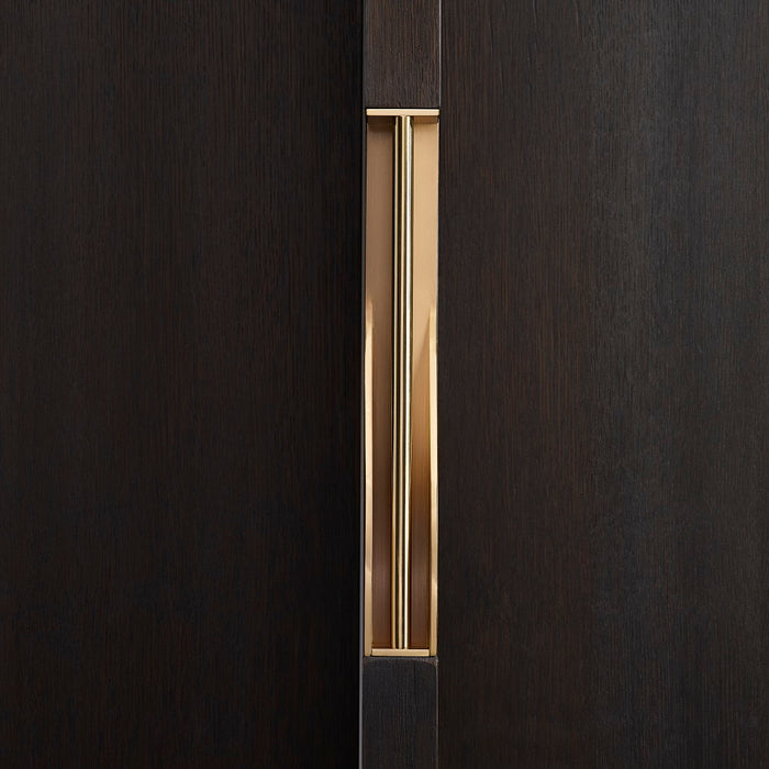 Elegant brass dressing handle on a dark wood door from the front. Beautifully and functionally designed.