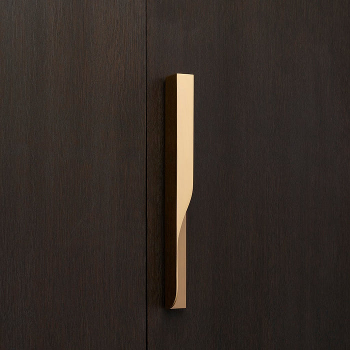 Elegant brass furniture pull handle on wood door from the front. Beautifully and functionally designed.