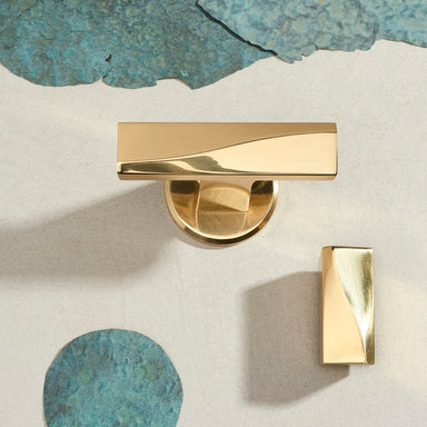 Elegant brass furniture knob with matching Olivette with aged copper pieces around them from above. Beautifully and functionally designed.