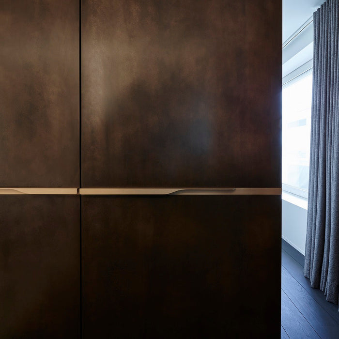 Minimal brass furniture pull handle on wood door from the front. Beautifully and functionally designed.