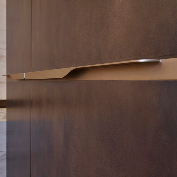 Elegant brass furniture pull handle on wood door seen on an angle. Beautifully and functionally designed.