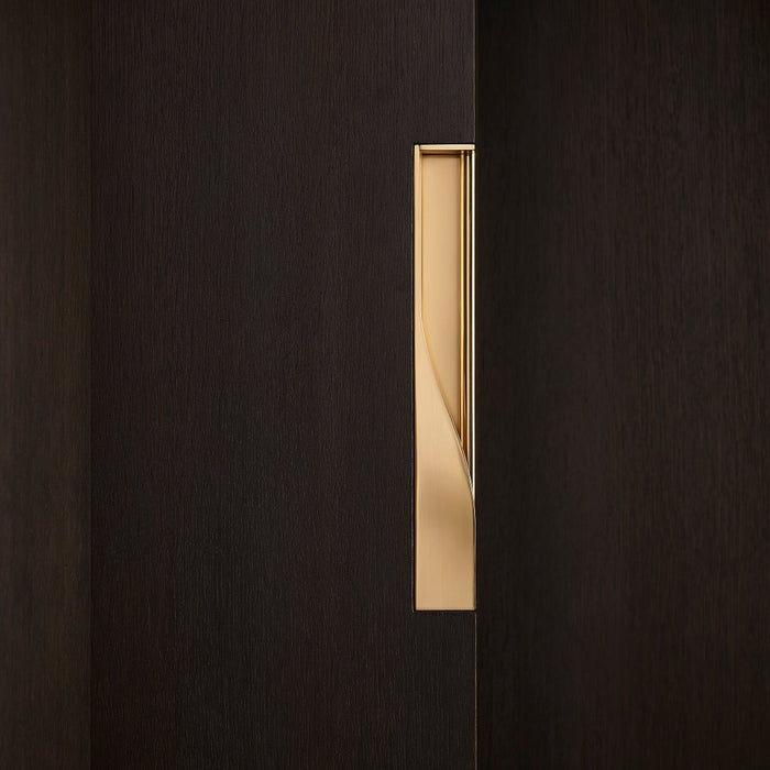 Elegant brass dressing handle on a dark wood door from the side. Beautifully and functionally designed.