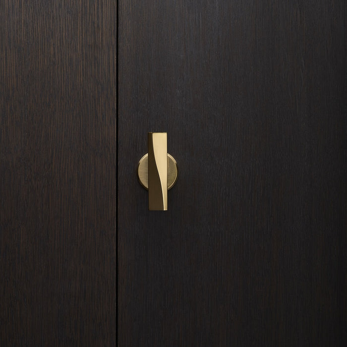 Elegant brass door knob with round rose on a dark wood door. Beautifully and functionally designed.