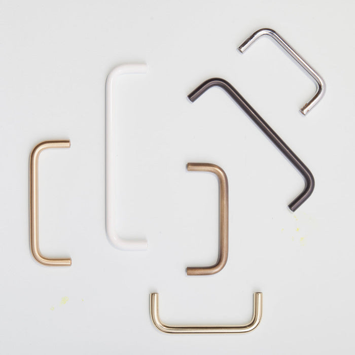 A variety of Charlie Bar Pull Handles in different sizes and finishes placed haphazardly.