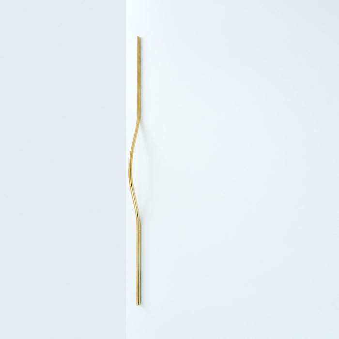 Elegant long brass line handle on a white door.