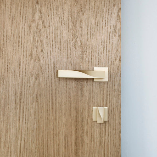 Elegant brass lever handle with square rose and thumb turn on light wood door. Beautifully and functionally designed.