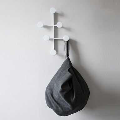 Modern and minimal white coat hanger with gray bag.