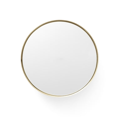 A finely designed wall mirror within a brass bowl.