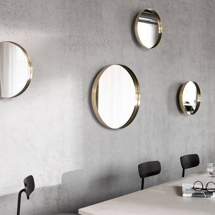 Menu Darkly Mirrors in brass on wall behind bar. Circular shape designed in Denmark.