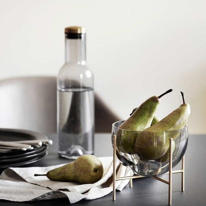 Elegant small bowl filled with pears sitting on a dining table with a modern bottle of water and a table setting..