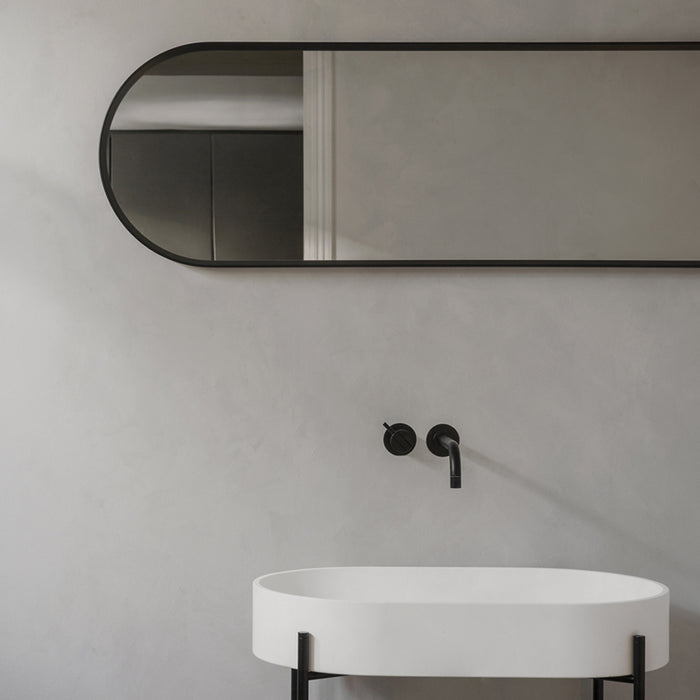 Offered in either black or white, this oval wall mirror has rounded edges and clean lines.