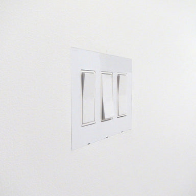Flush recessed wall outlet plate. Minimal architectural detail.