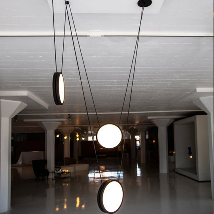Matte black pendant lights balanced on individual wires