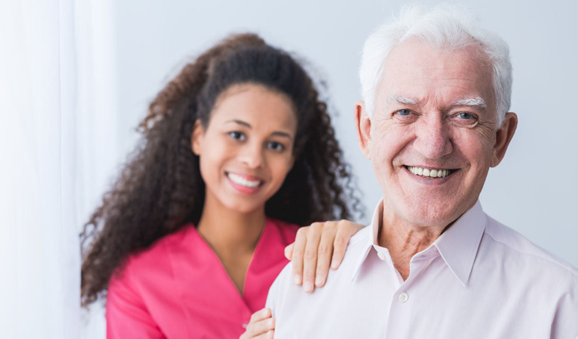 Happy carer and smiling senior man standing in light interior