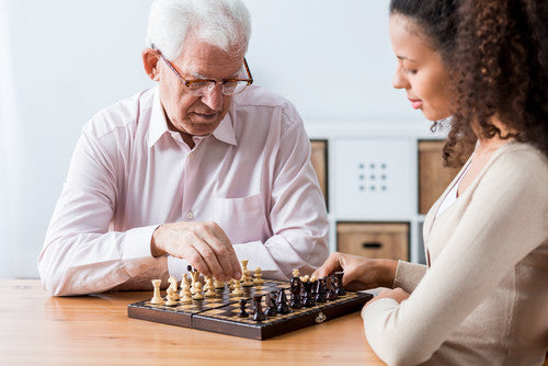 Photo of retiree and caregiver playing chess