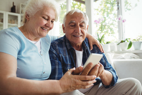 Senior-couple-using-mobile-phone-at-home