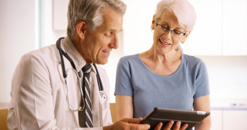 Senior-doctor-talking-with-elderly-woman-patient-in-the-office-with-tablet