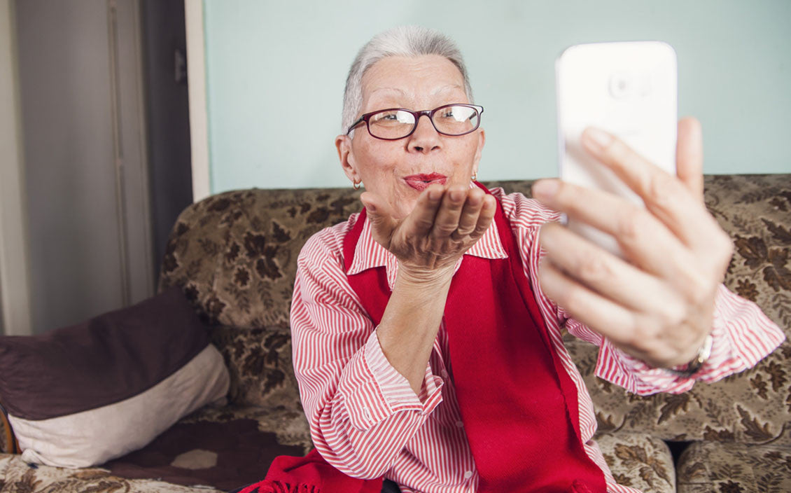 Senior old woman sending love and kisses to her family over skype or viber using her cellphone