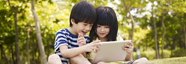 Two children watching an iPad in the park