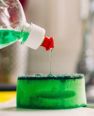Washing up liquid pouring on to a kitchen sponge