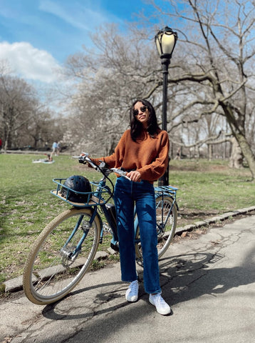 Claire Stern Popsugar posing with a black crocodile helmet and her bike in New York
