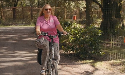 Carole Baskin cycling through her sanctuary with a Sawako Helmet