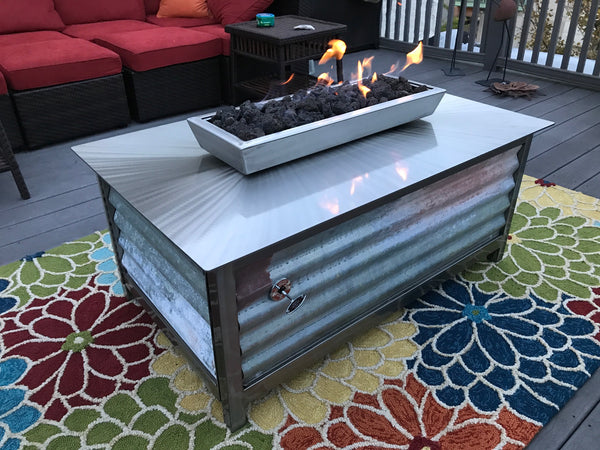 Gas Burning Stainless Steel IMPACT Fire pit table on a rooftop deck in downtown Philadelphia Pennsylvania with the comcast buildings in the background