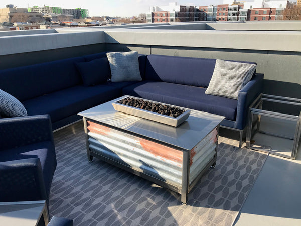 gas burning stainless steel outdoor IMPACT Fire pit table on a rooftop in south central downtown Philadelphia Pennsylvania