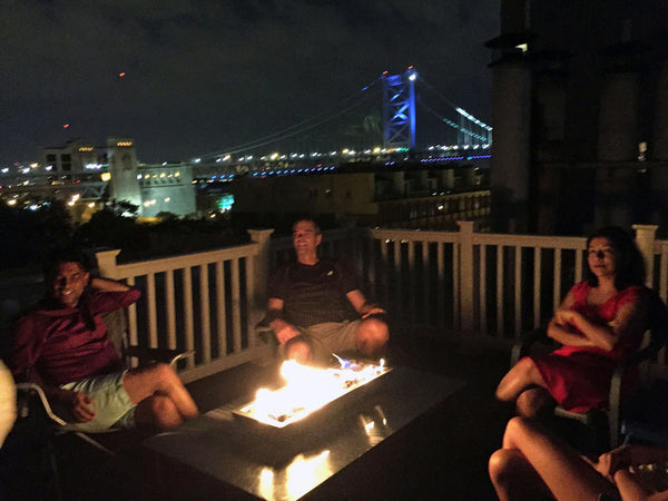 enjoying an IMPACT Fire Table on a rooftop in Philadelphia with the Ben Franklin Bridge in the background