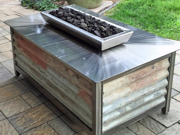A premium, heavy duty, hand brushed and powder coated clear, stainless steel rectangular firepit or fire pit with salvaged reclaimed corrugated steel side panels for burning natural gas or propane on your deck, patio or garden area, made in America