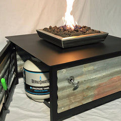 Picture of a standard propane tank on its tank holder just inside the access door of a square shaped IMPACT Fire Table