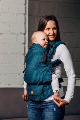 Front facing image of a woman wearing her infant in a blue and teal tessera weave LennyUpGrade adjustable baby carrier.