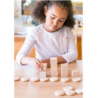 A child stacking wooden blocks alongside the corresponding Grapat number counting coin - Canada