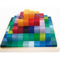 A pyramid of different length 4x4cm rectangular blocks in a rainbow of colours stacked in a natural wood tray