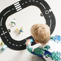 A child is sitting on the floor playing with cars on a WayToPlay, rubber roadway circular track.