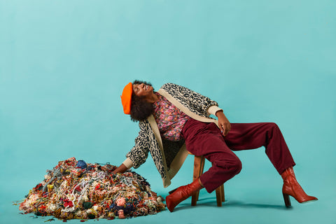 A woman wearing brown boots, burgundy trousers, colorful sweaters and an orange beret is sitting next to a pile of scrap yarn.