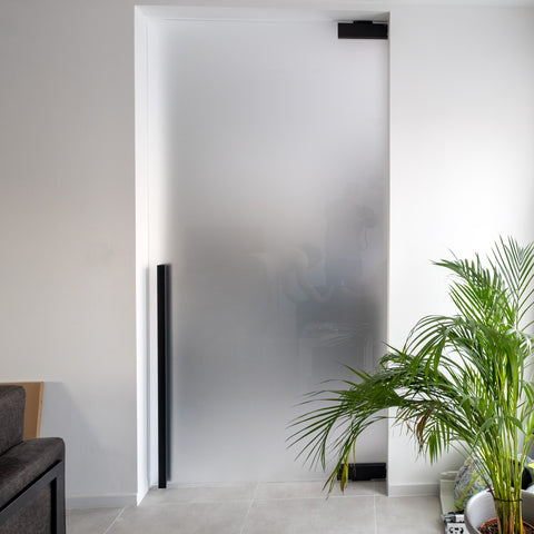 Etched glass pivot door with black hardware