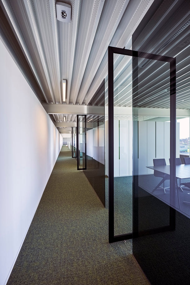 Glass pivot door installed in between glass office partitions