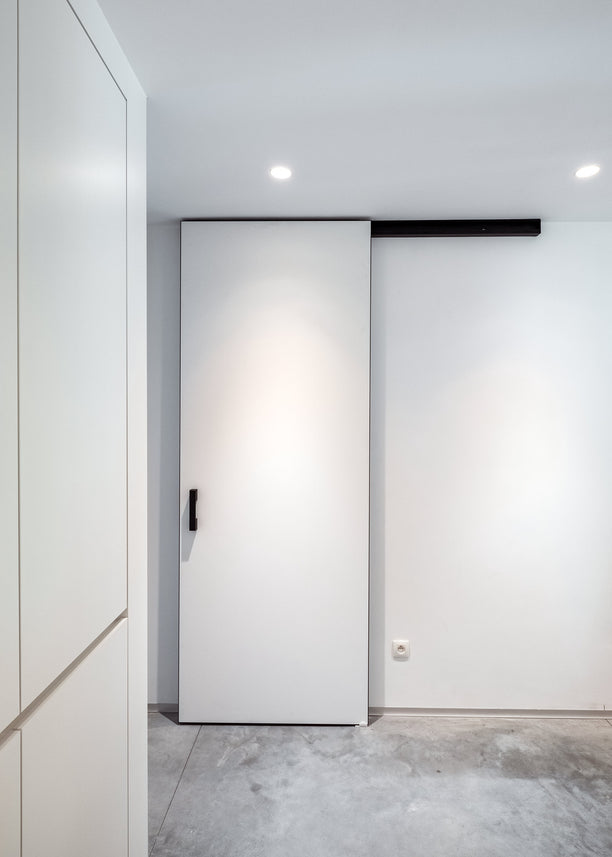 Modern white sliding door with black rail and handle