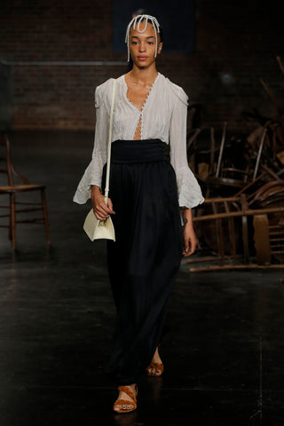 the-elliot-top-in-ivory,the-rosie-pant-in-black,the-small-nellie-structured-frame-bag-in-cream-leather,the-braided-sandal-in-cognac