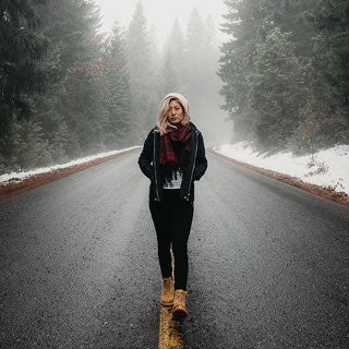 A woman walking down a winter road.