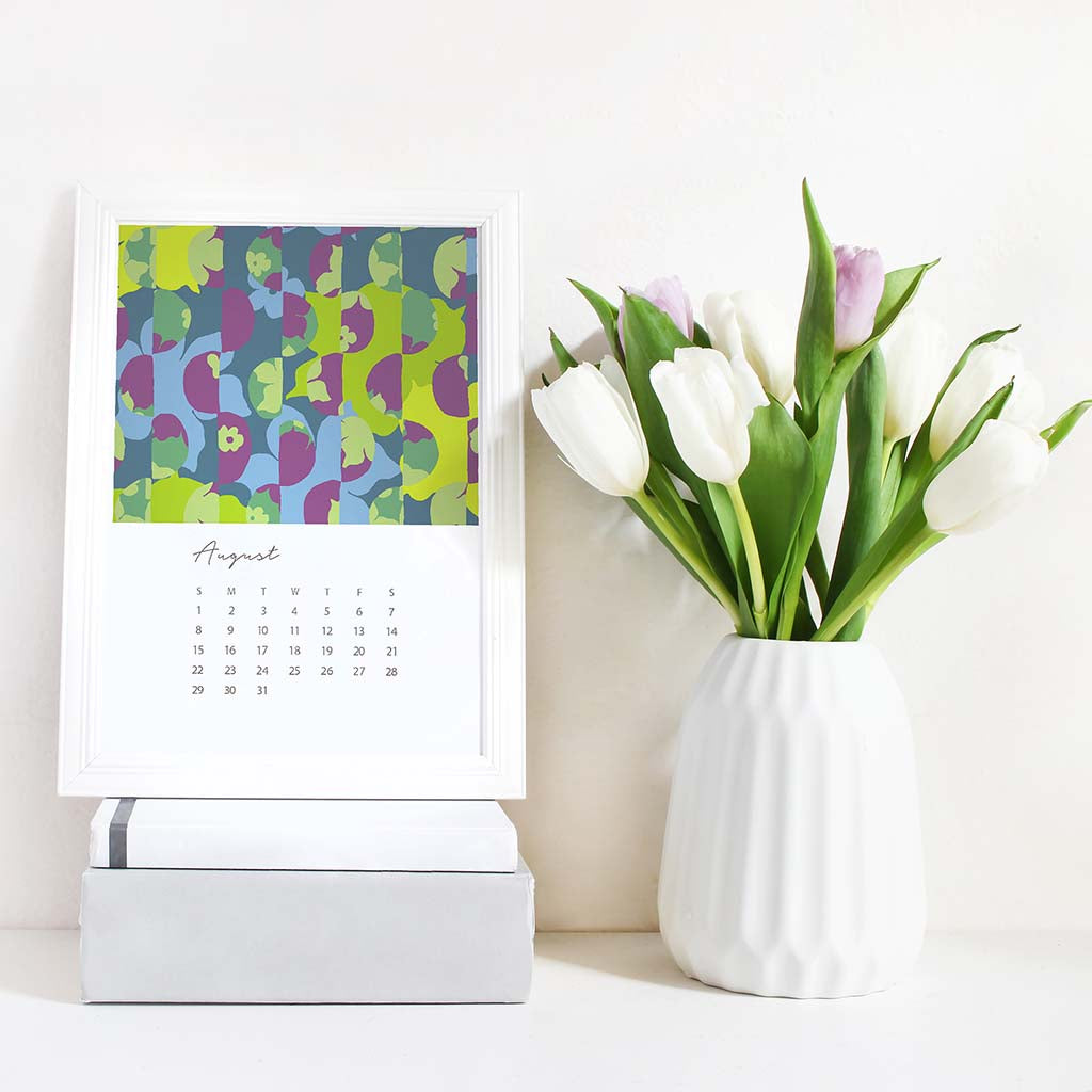 2021 Desk Calendar shown on desk in white frame on stack of books. Month of August is shown with bold graphic shapes in blue, green, and purple. White vase with white and purple tulips shown next to framed calendar on desk.