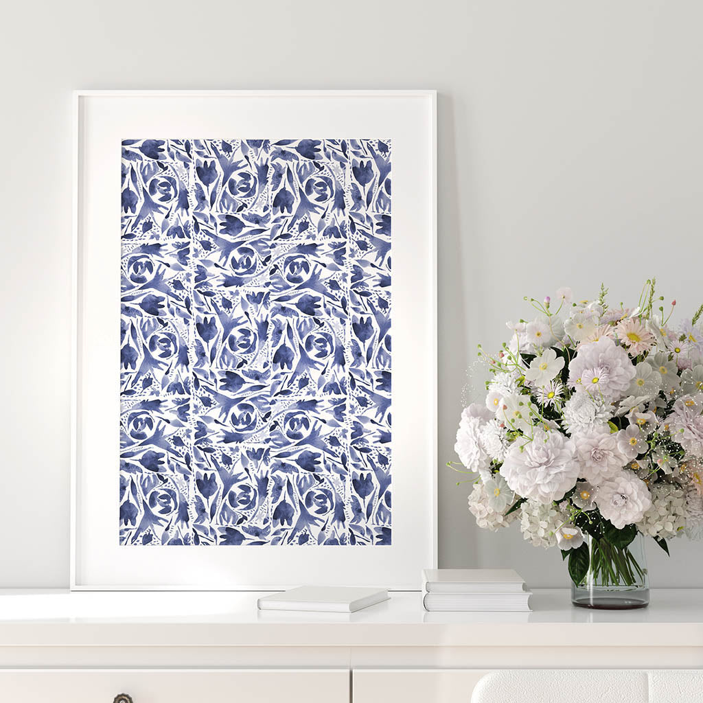 Indigo watercolor folk design art print shown at 16x20 inches in a white frame leaning up against a gray wall. White and pink flowers on white sideboard next to frame